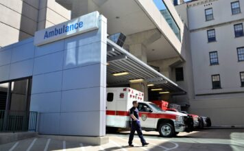 An emergency medical technician walks in front of an ambulance parked at a Hospital emergency wing.